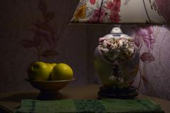 Still life by the light of lamp, a vase with apples in Stock Photo