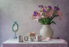 Still life with a lily, freesia, mirror and letters with the word love. Still life with a lily, freesia with a white vase, a mirror for girls and letters with royalty free stock image