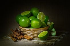 Still life, lime fruit in a wicker basket, cinnamon, dark background royalty free stock photos