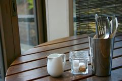 Still life lunch scene. Still life scene showing milk jug, sugar cubes in glass jar, knife, fork and spoon in metal vase on a wooden table Stock Photography