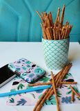 Still life made of objects - salt sticks in a mug, plys - salt sticks in a mug, plastic card box, pencil and a postcard. Still life on a writing table - salt Stock Images