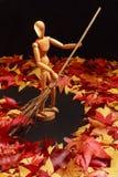 Artist`s Manikin Sweeping Autumn Leaves royalty free stock photo