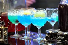 Colorful cocktails with ice on nightclub bar counter. Still life with many colorful cocktails with ice in wine glasses on cafe bar counter closeup stock photography