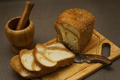Still life with marble bread and a mortar. Simple still life from village kitchen - marble bread in eastern european style, wooden mortar and an old rural knife stock images