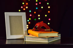 Still life with mask on book and picture frame on  wooden table Royalty Free Stock Photography