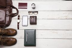 Still life with Men`s casual outfits with leather accessories on. Brown wooden background, beauty and fashion, travel concept Stock Photo