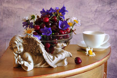 Still life with a merry and cupid. On a stand a dish stands with a merry, alongside white cup with a saucer and cupid Stock Image