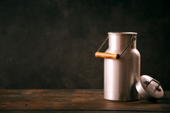 Still life with metal vintage milk can. Standing on wooden countertop Royalty Free Stock Photography