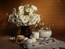 Still-life with milk. Still-life with milk, eggs and colors in a vase Royalty Free Stock Photos