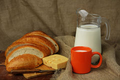 Still life with milk and bread. Still life with a milk jug, an orange mug, bread and cheese Stock Photo