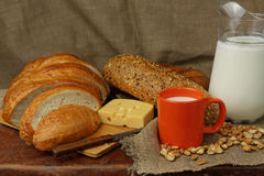 Still life with milk, cheese and bread. Still life with a milk jug, an orange mug, bread and cheese Stock Photos