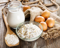 Milk, cottage cheese, eggs and flour on wooden table Royalty Free Stock Image