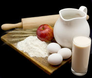 Still-life with milk and eggs. Milk, eggs, flour, apple and wheaten ears on  wooden board Royalty Free Stock Image