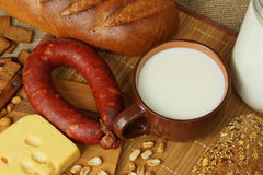 Still life with a milk mug, bread and sausage. Still life in rural style with a milk mug, bread, cheese and sausage Royalty Free Stock Image