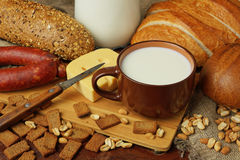 Still life with a milk mug, cheese, bread and sausage. Still life in rural style with a milk mug, bread, cheese and sausage Stock Image