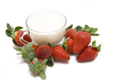 Still life with milk and strawberry. Glass cup with milk and a strawberry. A still-life on a white background Royalty Free Stock Photography