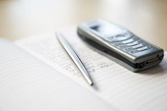 Still life of mobile phone and silver pen resting on notebook Stock Image