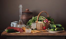 Still life with moonshine, fresh vegetables and sausage. Still life with moonshine, fresh vegetables in the basket and sausage in a rustic style royalty free stock photography