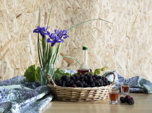 Still life with mulberry and iris. Still life with mulberry in a wicker basket, a bottle of cognac and irises in a vase close-up Royalty Free Stock Photography