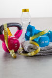 Still-life of natural body care and gym toning up. Still-life of kettle bells, dumbbells, grey towel, measuring tape and water for natural body care and toning Royalty Free Stock Photos