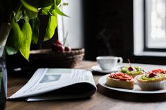 Still life of newspaper, breakfast with cakes and hot coffee on kitchen table in front Royalty Free Stock Image