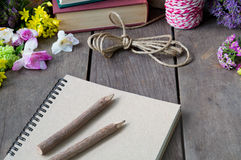 Still life of note book around nice flowers on wooden table Royalty Free Stock Photos
