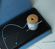 Still life. notebook, old spool of thread with a needle, pins, scissors. close-up. Royalty Free Stock Photography
