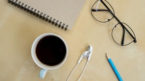Still life with notebook , pencil, Earphone , glasses Stock Photos