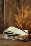 Still life with notebooks and flower foxtail weed on wooden background Royalty Free Stock Photo