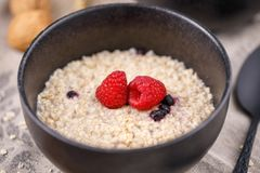 Still life with oatmeal and fresh raspberries in a refined bowl. Useful breakfast. Close-up Stock Photography