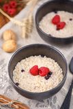 Still life with oatmeal and fresh raspberries in refined bowls. Close-up Stock Image