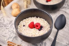 Still life with oatmeal and fresh raspberries. Useful breakfast. Close-up Stock Image