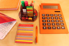 Still Life of office desktop in orange color. Calculator, daily planner and orange colored stationery Stock Image