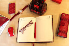 Still Life of office desktop for women. Open daily planner, computer, cell phone, business card holder, sunglasses, watches and stationery in red style Royalty Free Stock Image