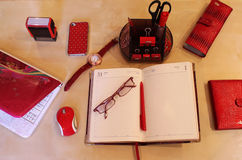 Still Life of office desktop for women. Open daily planner, computer, cell phone, business card holder, sunglasses, watches and stationery in red style Stock Images