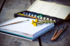 Art supplies, sketchbook and bouquet of flowers coltsfoot stock image