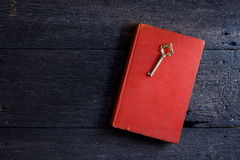 Still life with old book and key on wooden Royalty Free Stock Images