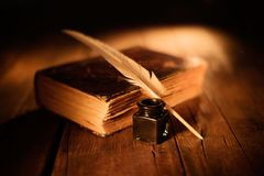 Old book with quill pen and inkwell on wooden table stock photography