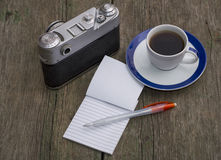 Still life the old camera, a notebook and coffee, on an old tabl Stock Photos