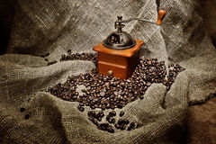 Still life with old coffee grinder and beans on burlap. Background Stock Photo