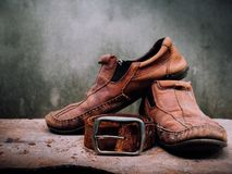 Still life old Leather shoes and belt. It more of dirty and  sha. Bby skin. Time to change new shoes or repair Stock Images