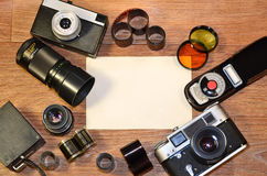 Still-life with old photography equipment. Retro camera and some old photos on wooden table. Vintage mock up for artwork or logo design presentation with film Stock Photo