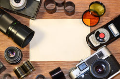 Still-life with old photography equipment. Retro camera and some old photos on wooden table. Vintage mock up for artwork or logo design presentation with film royalty free stock photography
