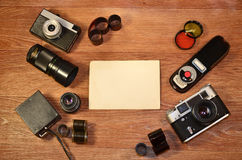 Still-life with old photography equipment. Retro camera and some old photos on wooden table. Vintage mock up for artwork or logo design presentation with film Stock Images