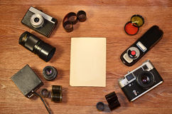 Still-life with old photography equipment. Retro camera and some old photos on wooden table. Vintage mock up for artwork or logo design presentation with film royalty free stock images