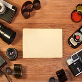 Still-life with old photography equipment. Retro camera and some old photos on wooden table. Vintage mock up for artwork or logo design presentation with film royalty free stock photos