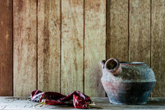 Still life old pot and dry pepper. On brown background Royalty Free Stock Photo