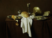 Still life, old style image of bread, cheese, olives, oranges on. A brown table and brown background Royalty Free Stock Photo