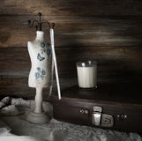 Still Life with an old suitcase, a glass of milk and a mannequin sewing on a background of a rough wooden wall.  royalty free stock image