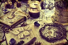 Still life with old tarot cards, runes, roots and black candle on table royalty free stock images